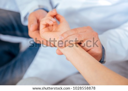 Taking care of your health. Close up of medical worker putting his fingers on a wrist of a female patient while checking her pulse during an appointment. Foto stock ©