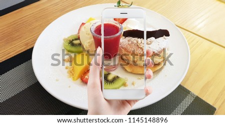 Taking food photo, dessert photography by smart phone,Hands with the phone close-up pictures of food. Breakfast homemade. girls take food photos on the phone a smartphone sweet Pancake with fruit.