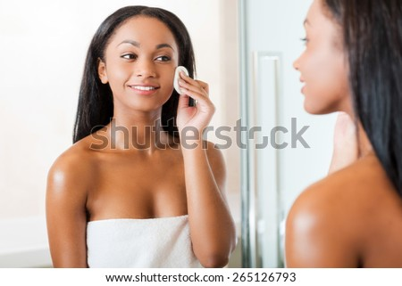 Taking good care of her face. Beautiful young African woman cleaning her face with sponge and smiling while standing against a mirror in bathroom