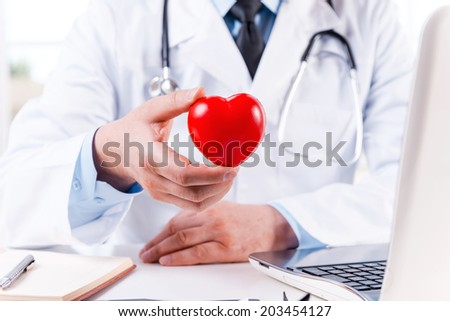 Taking good care of your heart. Close-up of doctor holding heart shape toy while sitting at his working place #203454127