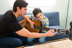 Taking guitar classes with a private music teacher. Hispanic young man helping an elementary boy to play the guitar during home lessons