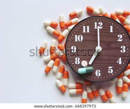 Taking medicine time concept, pills on clock and around on white background #668397973