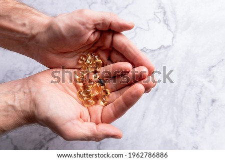 Taking Natural Supplements for Health.pharmaceutical ,sport and diet concept, vitamins and medication.Girl accepts the fish oil.hand holds yellow medication capsules.blood cholesterol,brain healthy.