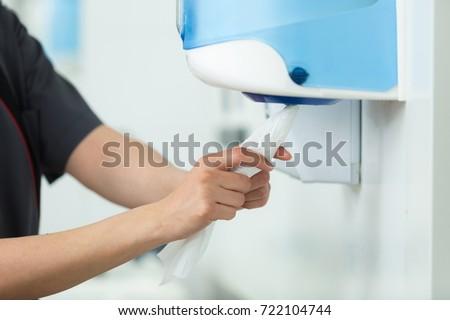 taking paper from tissue dispenser