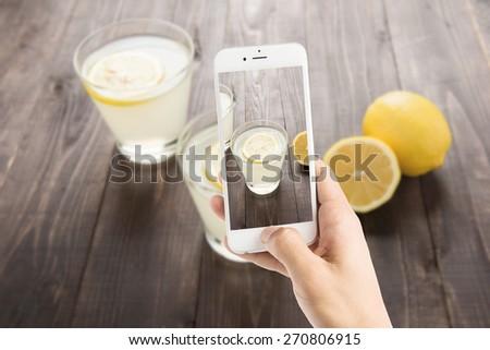 Taking photo of freshly squeezed lemon juice in glasses
