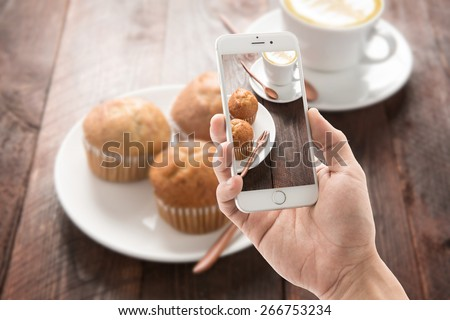 Taking photo of muffin and coffee on wooden table.