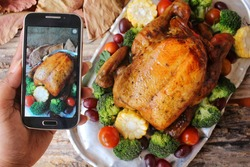 Taking photo of roasted turkey with vegetables for thanksgiving day