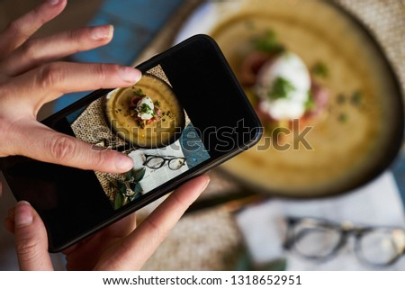 Taking photo of toast with poached eggs, bacon, beans, truffle oil, avocado and pickled onions. Woman hands with smartphone taking photo of business breakfast food on wooden table background