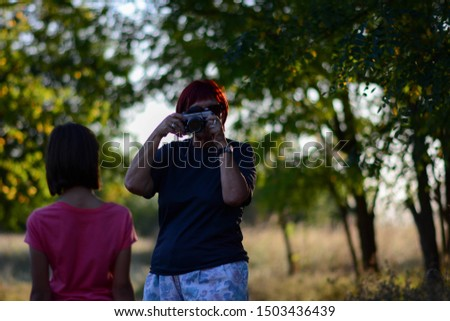 Taking photo with camera of young girl, outdoor summer. Senior woman taking photo with camera of young girl, trees background.
