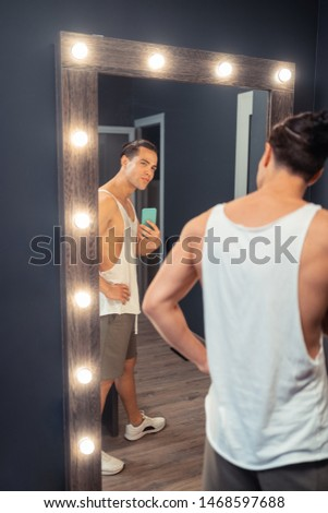 Taking photos. Attractive fit man holding his modern smartphone while taking photos in the mirror