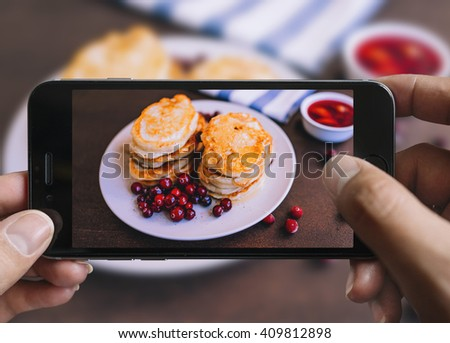 Taking picture of pancakes with mobile phone in female hands.Plate is on a black aged wooden table. Vintage style.