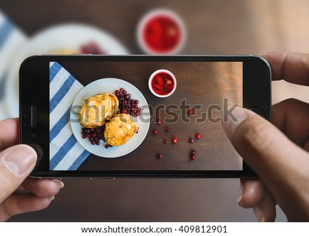 Taking picture of pancakes with mobile phone. Phone in male hands.On the plate there is pancakes with berries and honey. Plate is on a black aged wooden table. Vintage style.