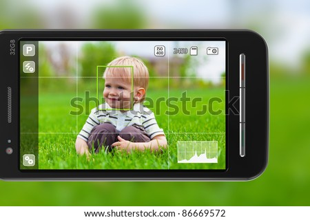 Taking pictures with mobile phone: smartphone in camera mode outdoors