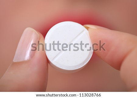 Taking pills Close-up of a white pill in woman's fingers.