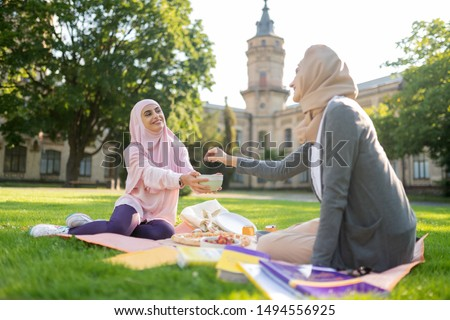 Taking some berries. Muslim woman wearing hijab taking some berries while having lunch with friend