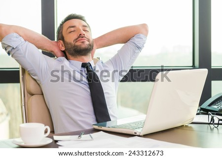 Taking time for a break. Handsome mature man in shirt and tie holding hands behind head and keeping eyes closed while sitting at his working place #243312673