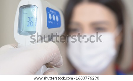 Taking woman 's temperature with thermometer to find infected by coronavirus, Covid-19. Close up shot. Foto stock ©