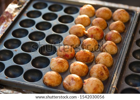 Takoyaki, a ball-shaped Japanese snack, being cooked in a special molded pan. Takoyaki are filled with minced and diced octopus. Kansai speciality street food.