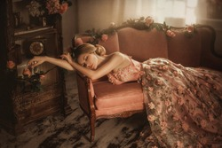 Tale of Sleeping Beauty in the old, abandoned vintage room. It covered the dust and roses. Summer autumn atmosphere of sadness. Creative warm pastel colors. Princess lies in a luxurious floral dress