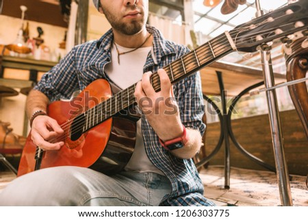 Talent in music. Close up of strong male hands pressing strings and mastering chord on guitar #1206303775