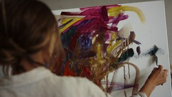 Talented female artist creating picture with palette knife in modern studio. Creative woman using easel and canvas for work in art studio. Inspired painter drawing colorful artwork indoors.