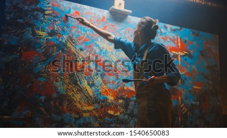 Talented Female Artist Energetically and Enthusiastically Using Paint Brush She Creates Modern Masterpiece of the Oil Painting. Creative Studio with Large Canvas of Striking Colors. Low Angle Shot Photo stock ©