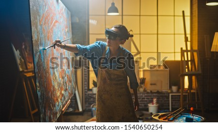 Talented Female Artist Wearing Augmented Reality Headset Working on Abstract Painting, Uses Paint Brush To Create New Concept Art Using Virtual Reality Interface. High tech Creative Modern Studio