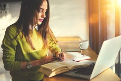 Talented female student of journalism creating article for homework using textbook and web sources searching information writing down ideas into copybook sitting in coworking space with laptop