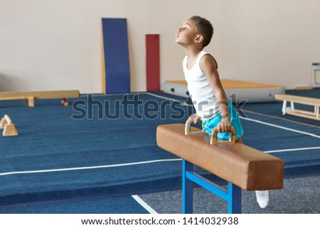 Talented hardworking African boy training indoors at gym, balancing on pommel horse, working on strength, endurance and agility. Fitness, gymnastics, sports, children and motivation concept
