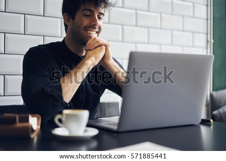 Talented male editor of popular magazine starting working day monitoring morning news on websites choosing main theme for front page using modern laptop computer and wireless connection to internet