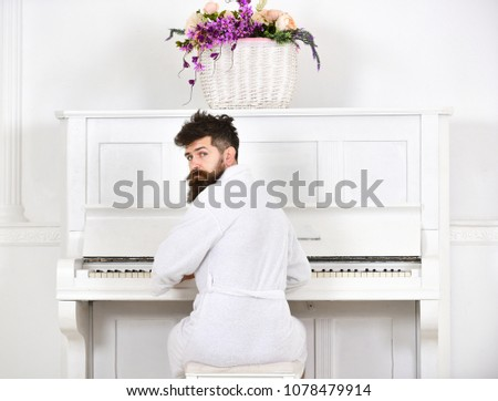 Talented musician concept. Man sleepy in bathrobe sit in front of piano musical instrument in white interior on background, rear view. Man in bathrobe enjoys morning while playing piano.