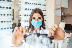 Talented skillful optician choosing lenses for trial spectacles, Young beautiful girl ophthalmologist working on trial glasses in her ophthalmology clinic.