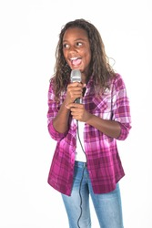 Talented young diverse singer singing into a microphone. Cute African American girl singing with energy and performing on stage. Isolated on a white background