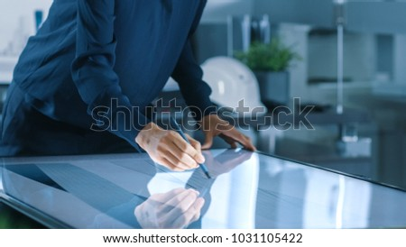 Talented Young Female Architectural Designer Draws Building Concept on a Graphics Tablet Display Vertical Touchscreen Table. Clean Minimalistic Office, Concrete Walls Covered by Blueprints. #1031105422
