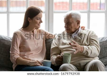 Talk during teatime with aged man, caregiver listens life memories stories of old 75s patient seated on sofa in cozy living room. Provide support care and attention of older generation people concept