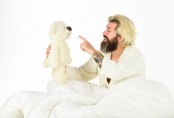 talk to you. feel childish. bearded man hipster play with bear. toys for adult. feeling happy and childlike. Psychological problems with imaginary friends. good morning. mature man with toys in bed.