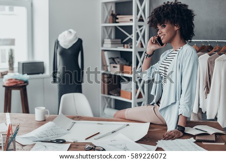 Talking about fashion. Beautiful young African woman talking on smart phone and looking away while sitting on desk in her workshop  - Shutterstock ID 589226072