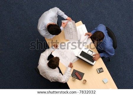talking about plans - three working business people over plans.Aerial shot taken from directly above the table