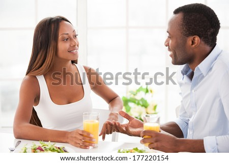 Talking at the breakfast table. Beautiful young African couple sitting together at the table and having breakfast