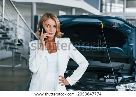Talking by phone. Woman in formal clothes is indoors in the autosalon.