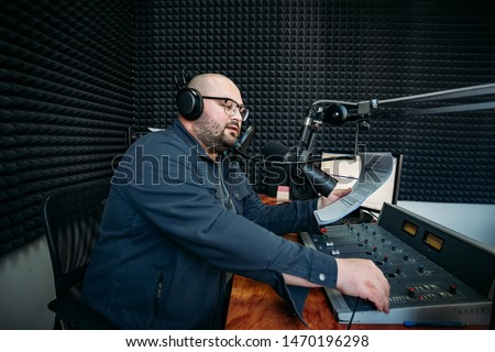 Talking male radio presenter read text on paper in radio station.