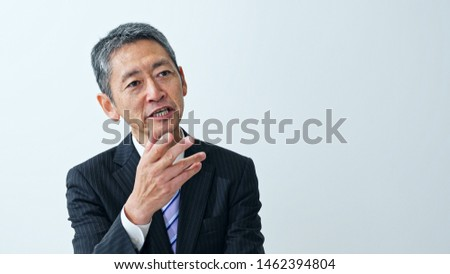 Talking middle aged asian businessman. Interview concept.
