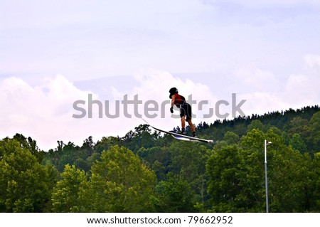 TALKING ROCK, GA/USA - JUNE 19: Unidentified man ski jumping during a  competition, June 19, 2011 in Talking Rock, GA at the  Whitestone Summer Starter Tournament. - stock photo