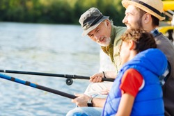 Talking to grandson. Bearded grey-haired grandfather talking to grandson while having family fishing