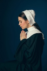 Talking to the moon at night. Medieval young woman as a nun in vintage clothing and white mutch sitting on the chair on dark blue background. Concept of comparison of eras.