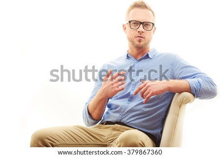 Talking young man. Portrait of handsome young man in casual blue shirt and dioptrical glasses sitting in comfortable pose isolated on white background