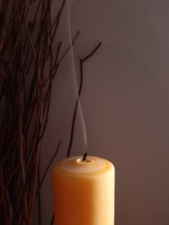 Tall beeswax pillar candle snuffed out, with one long trailing wisp of smoke