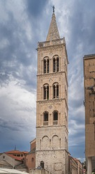 Tall bell tower of a St. Donata Church in early Romanesque architecture in Zadar old town, Croatia. Dramatic, stormy sky