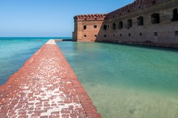 Tall brick walls of an old military fort on an island of Dry Tortugas. Florida. Blue sky, green water, beautiful summer day.