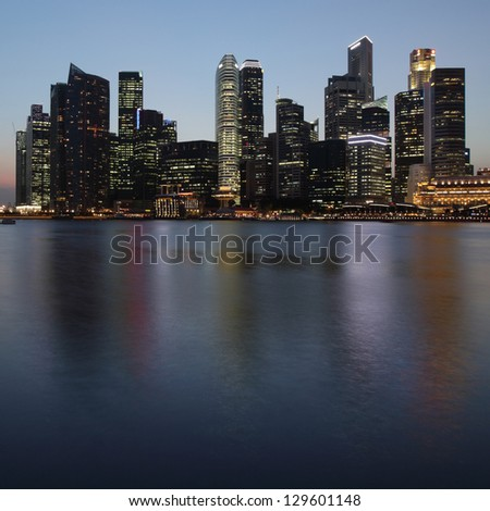 Tall buildings of a city reflected in a water at twilight